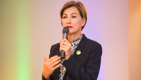 Kim Reynolds speaking at an event.